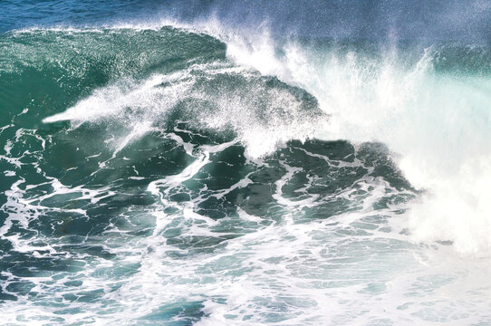 explosive surf across a white and green ocean.