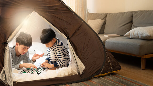 Indoor camping tent - Stay at home activity for family during Covid 19 pandemic lockdown concept. Young asian brothers kids playing games together in a teepee in living room missing travel. New normal