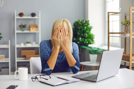 Frustrated senior woman covering face unable to deal with problem. Online fraud victim scammed on Internet crying, sitting at desk with laptop computer. Stressed mature lady having financial trouble