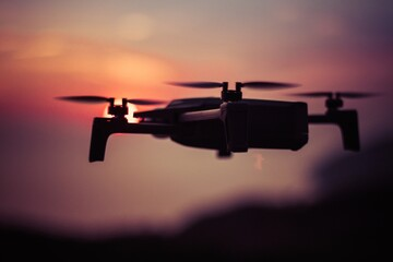 Close-up Of Silhouette Drone Against Sky During Sunset
