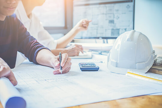 Architects Drawing Blueprint While Working In Office