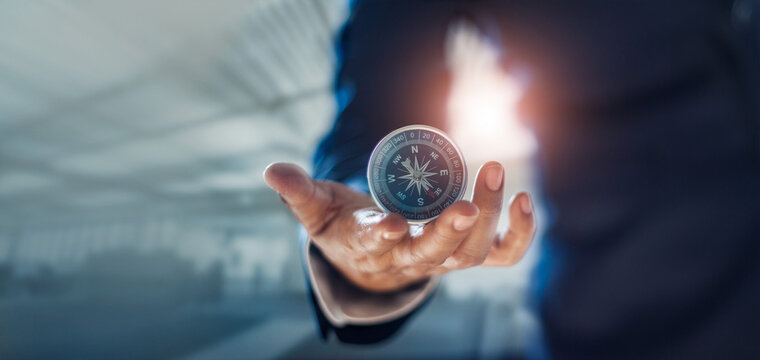 Businessman hand holding compass navigating business direction and successful strategic solution.Reflect accomplishment in terms of research and development growth market and financial profitability.