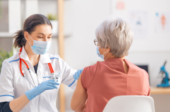Doctor giving a senior woman a vaccination