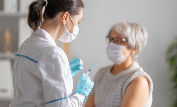 Doctor giving a senior woman a vaccination