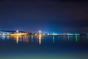 Obraz Illuminated City By Sea Against Clear Sky At Night - fototapety do salonu