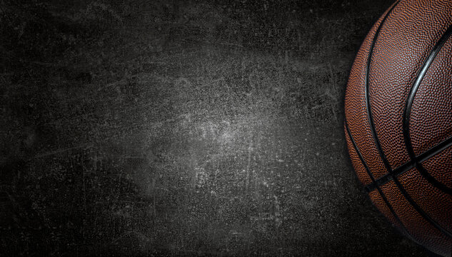 Basketball ball on dark concrete wall texture background. Background for product display, banner, or mockup