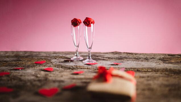 Coppia di bicchieri di champagne su tavola in legno antico. Tavola romantica per San Valentino o appuntamento romantico. Petali a forma di cuori, rose rosse, paio