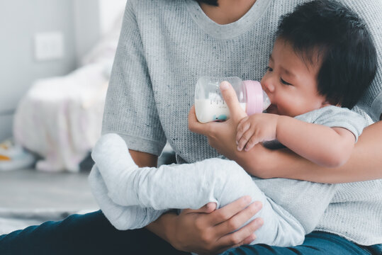 Young asian mother feeding baby from milk bottle.