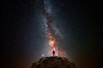 Fototapeta Man on top of a mountain observing the universe obraz