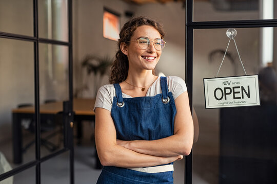 Small business owner standing at cafe entrance