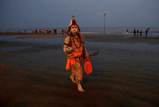 """A man dressed as Hindu Lord Shiva walks for alms from pilgrims at the confluence of the river Ganges and the Bay of Bengal ahead of """"Makar Sankranti"""" festival on Sagar Island"""