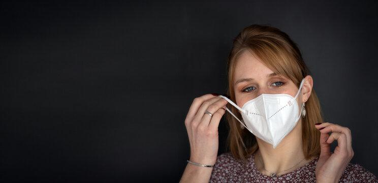 Junge blonde Frau zieht sich eine FFP2 Mundnasenschutz Maske auf - isoliert vor dunklem Hintergrund, Panoramaformat mit viel Textfreiraum für Header, Banner