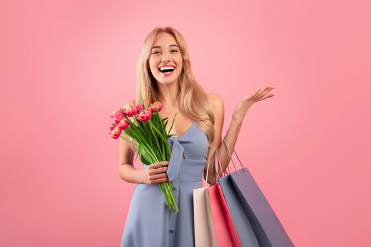 Happy young lady with shopping bags and bouquet of tulips buying gifts for spring holiday over pink studio background