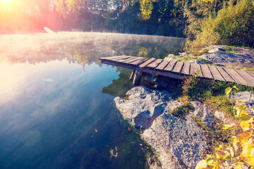 Wooden pier by the lake on a foggy autumn morning