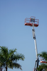 Photo articulating boom lift on blue sky with palm trees