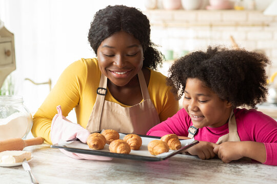 Black mother and daughter holding tray with fresh baked croissants in kitchen