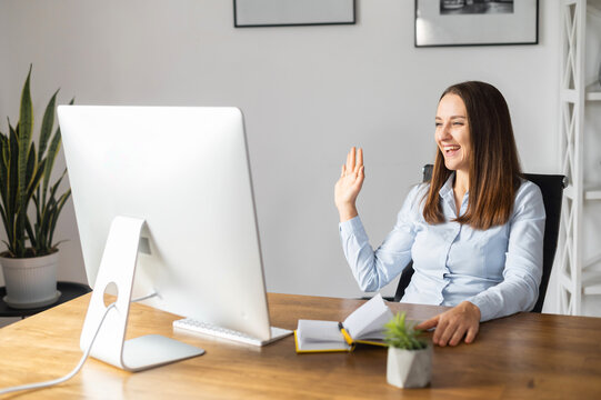 Cheerful female office employee in smart casual wear waving into webcam, talking online in virtual meeting sitting at the desk with PC in office