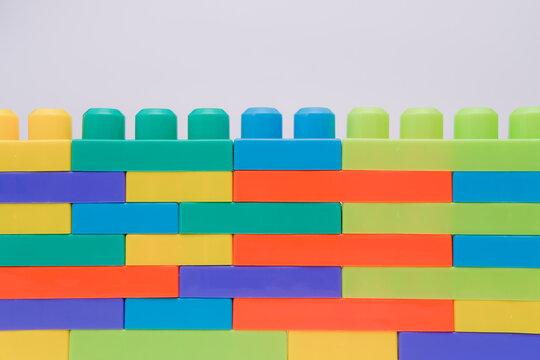 Multi-colour lego blocks wall on white background