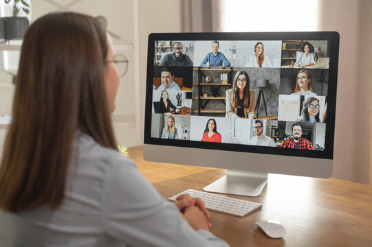 Brainstorm, online video meeting, virtual conference with multi ethnic coworkers, employee, colleagues. View over shoulder of a woman in formal shirt on a screen with webcam shots of diverse people