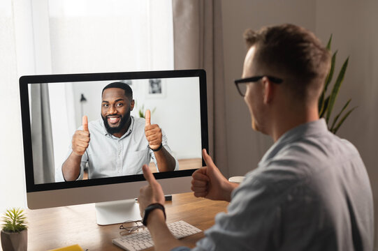 Video call, video meeting. A young man is discussing some business tasks with a young African man via video, they have come to a consensus and show thumbs up as a sign of successful negotiations