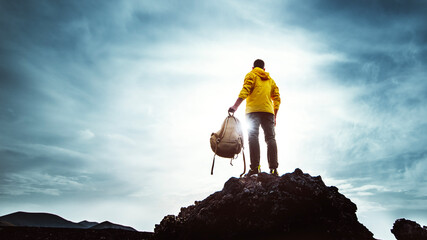 Young man with backpack standing on the top of a mountain at sunset - Goals and achievements