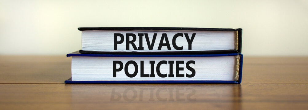 Privacy policies symbol. Concept words 'Privacy policies' on books on a wooden table. Beautiful white background. Business and privacy policies concept, copy space.