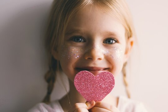 Cute blue-eyed little girl holding pink heart for valentines day. Lovely smiling child with heart. Hipster. Love.