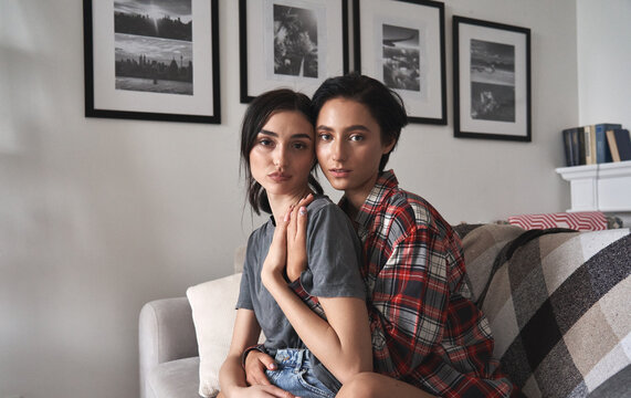 Portrait of young affectionate lesbian lgbtq couple hugging at home. Two beautiful women in love looking at camera, embracing, bonding, holding hands, enjoying time together. Lgbt relationship concept