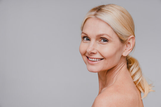 Side view portrait of good-looking mature blonde woman with clean skin smiling isolated over grey background