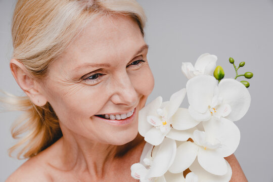Close up portrait of middle-aged beautiful woman with orchid branch isolated over grey background