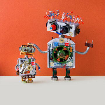 Creative design Robotic family. Big robot electrical wire hairstyle, plug arm. Small kid cyborg with lamp bulb toy. Copy space
