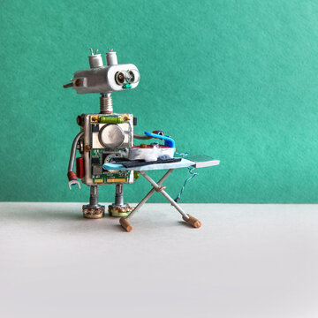 Robotics home service and future technology. Domestic robot ironing black trousers with iron and board. Green gray background, copy space.