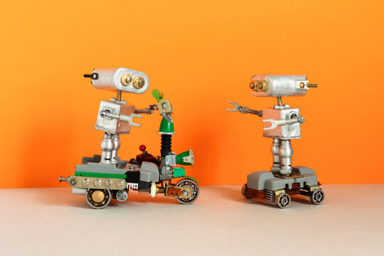 Robots drives an electric scooter and skateboard. Two simplified metal silver robotics toys on orange beige background.