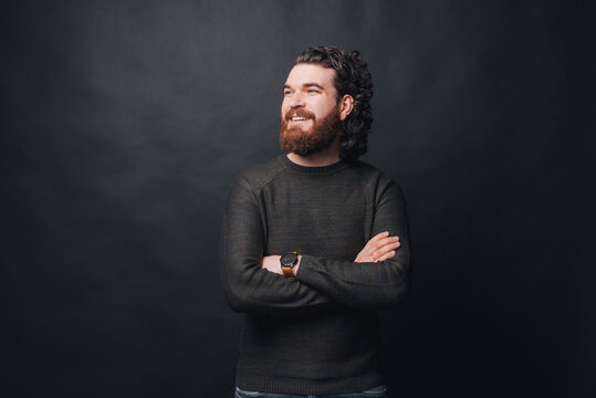 Handsome man with beard and long curly hair standing over dark background with crossed arms and looking away.