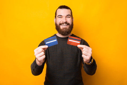 Joyful bearded handsome man showing two credit cards.