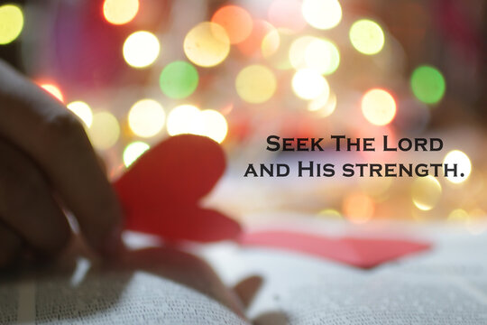 Christianity inspirational quote - Seek The Lord and His strength. Bible motivational words with blurry background of hand holding red love or heart paper shape and colorful bokeh light background.