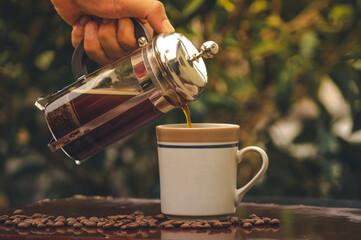 Preparando una taza de café en prensa francesa o cafetera de embolo con granos de café molidos en molinillo artesanal