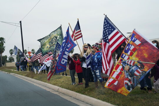 Supporters of U.S. President Donald Trump wave their flags near the airport where Trump will be landing after arriving in Harlingen in McAllen, Texas