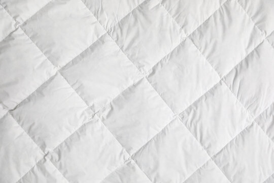Soft quilted blanket as background, top view