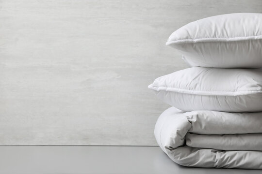 Soft folded blanket and pillows on light grey table, closeup. Space for text