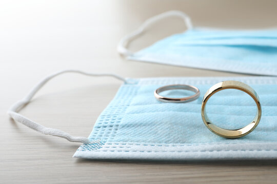 Protective masks and wedding rings on wooden table. Divorce during coronavirus quarantine
