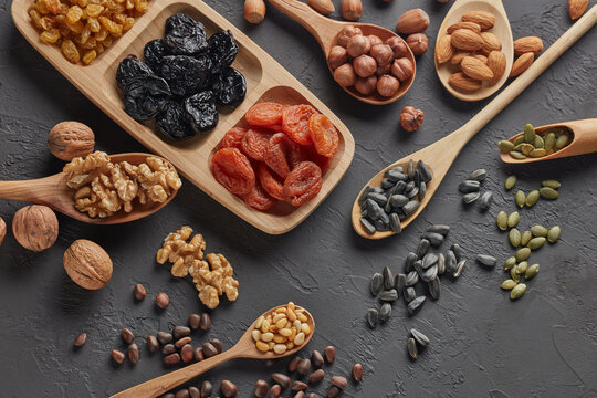 Different kinds of nuts, dried fruits in wooden spoones and dish on black slate background. Top view. Healthy food. Vegetarian nutrition