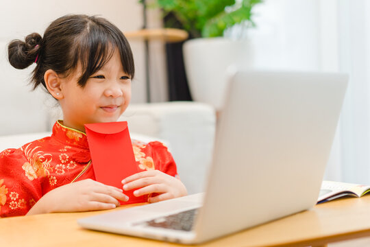 Happy chinese new year.Asian kid girl receive money online wearing chinese traditional qipao dress showing red envelope at home.Online party.Happy chinese new year covid19 lockdown.stay home holiday.