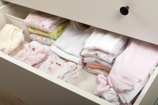 Cute newborn clothes in drawer