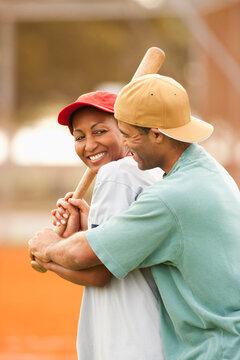 Man teaching girlfriend to play baseball