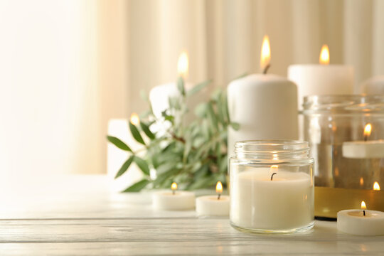 Burning scented candles for relax on white wooden table