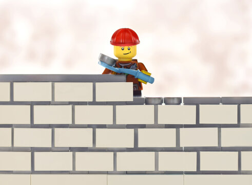 Editorial illustrative image to bricklayer occupation plastic lego minifigure toy by wall building.