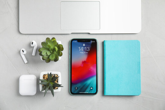 MYKOLAIV, UKRAINE - JULY 10, 2020: Flat lay composition with Iphone 11, MacBook laptop and AirPods on grey table