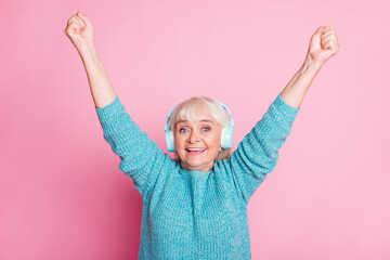 Photo of retired old lady raise hands dance wear headphones blue sweater isolated pink color background