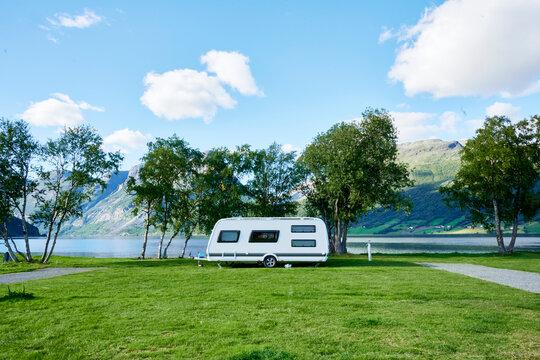 Toller Campingplatz mit Wohnwagen im Hintergrund Berge und See als Banner für Homepage